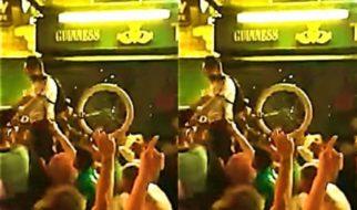 Irish fans help cyclist pass through the crowd at Euro 2016